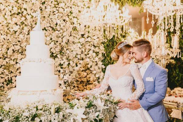 Mesa de bolo de casamento com noivos cortando o bolo