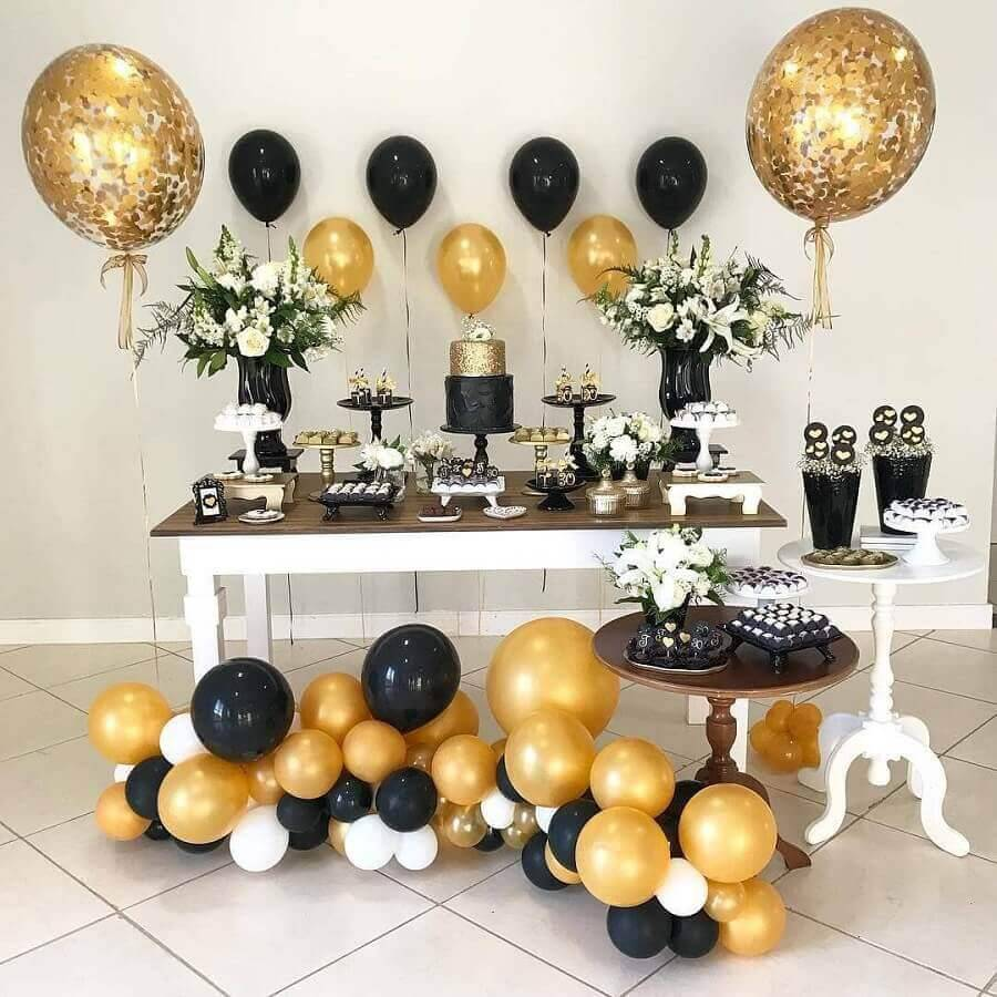 mesa de festa de aniversário com decorada preta e dourada  Foto Pinterest