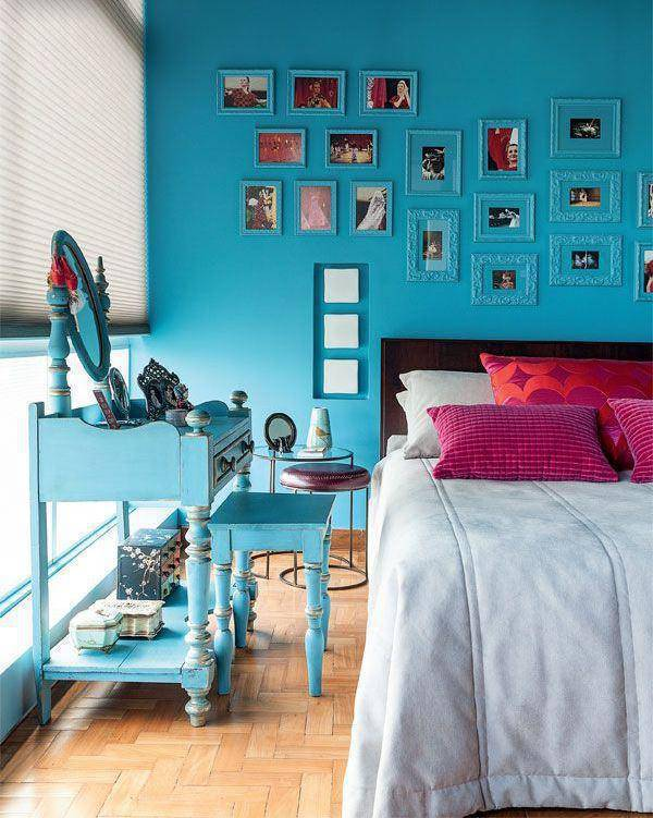 parede turquesa e almofadas rosa