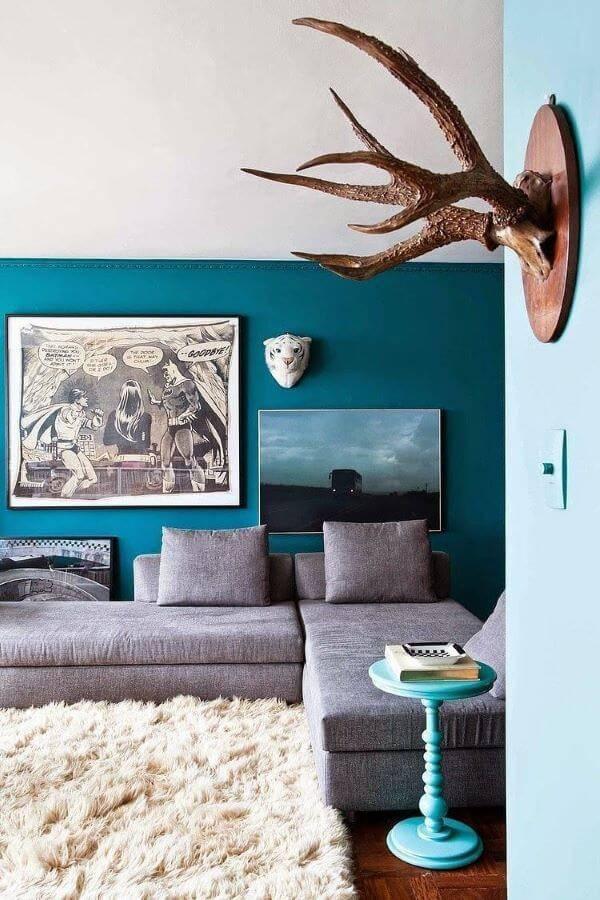 Parede azul com sofá cinza e tapete felpudo