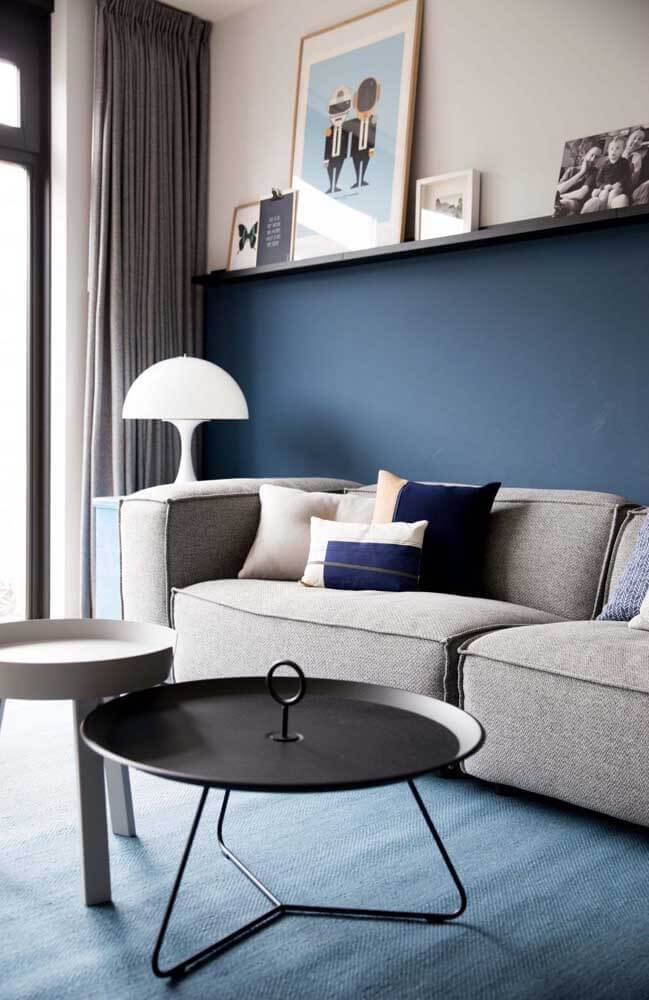 Parede azul marinho com sofá neutro