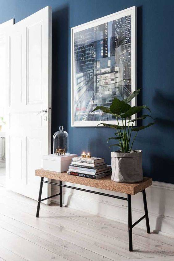 Parede azul na sala de estar com aparador rústico