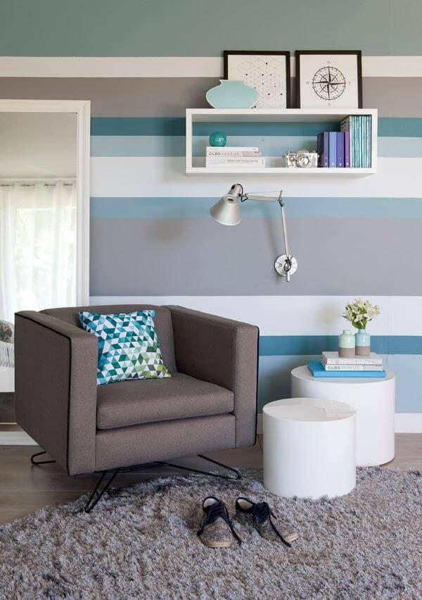 Parede azul listrada em tons neutros e poltrona confortável
