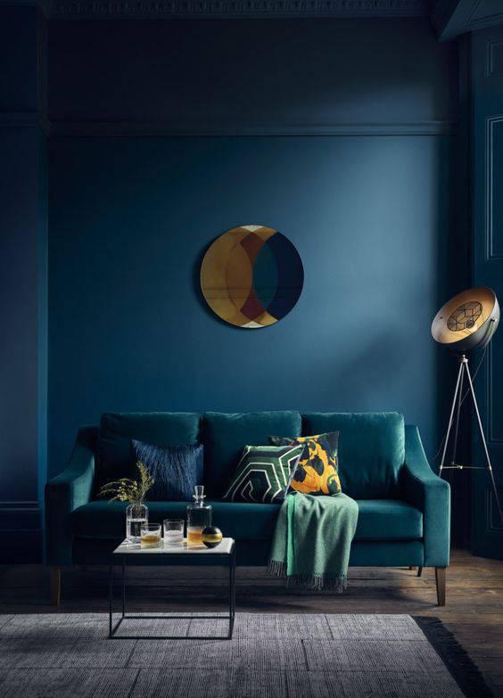 Parede azul escuro com sofá no mesmo tom
