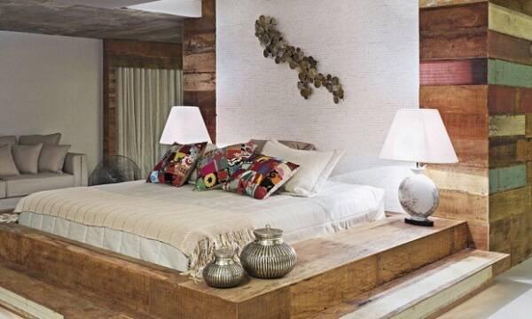 Quarto de casal com cama feita com acabamento de madeira