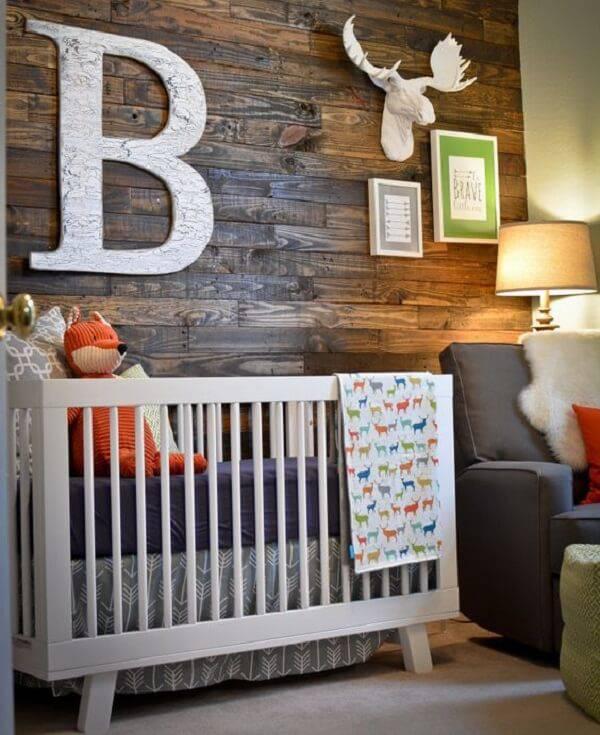Quarto rústico de bebê com parede de madeira e quadros decorativos