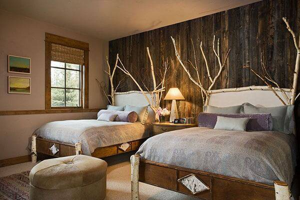 Quarto rústico compartilhado conta com camas de madeira e cabeceiras feitas com galhos