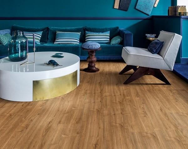 Sala de estar com sofá aveludado azul e piso laminado flutuante