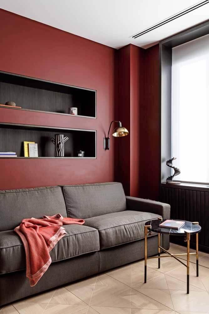 parede na cor vermelha e sofá cinza