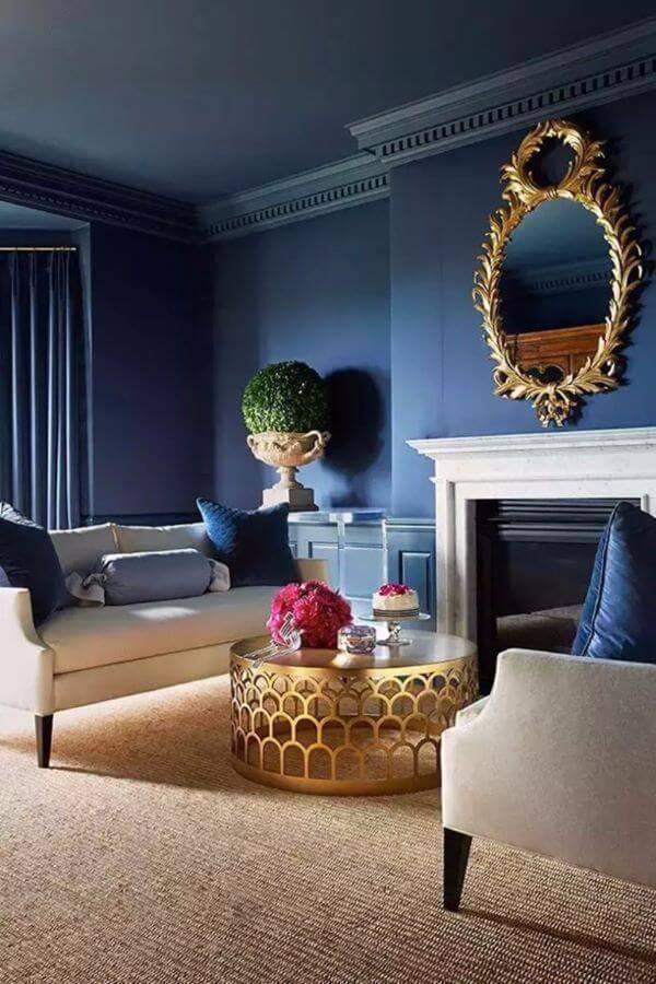 Sala de estar com parede azul e detalhes em dourado