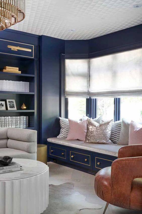Almofadas em rosa claro para contrastar com a parede azul marinho