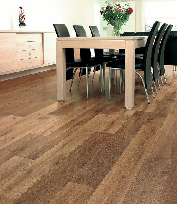 Sala de jantar com mesa retangular, cadeiras pretas e piso flutuante