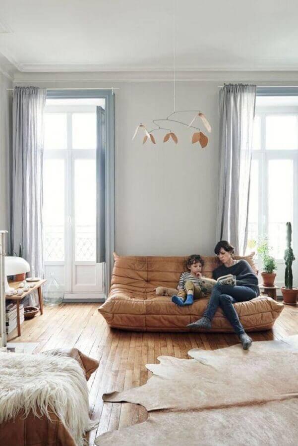 sala decorada com sofá sem braço e piso de madeira Foto Apartment Therapy