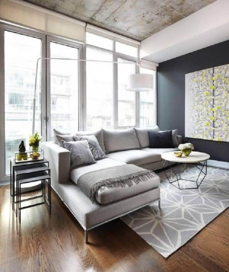 sala moderna decorada com sofá cinza e dois modelos de mesa de apoio Foto Dacasa