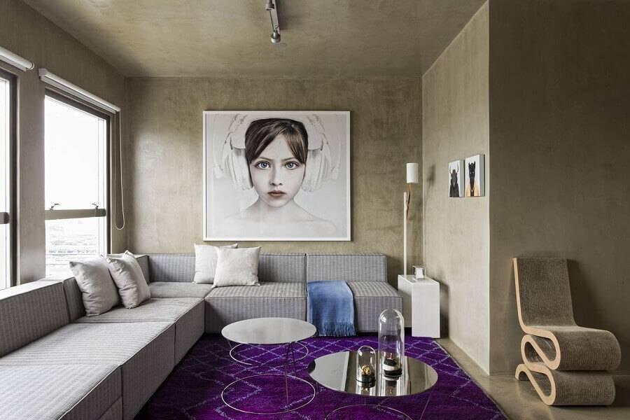 sala moderna decorada com sofá de canto sem braço e parede de cimento queimado Foto Archello