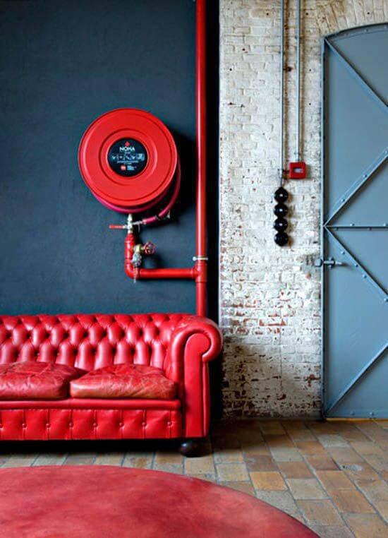 Sofá cor vermelha e parede azul combinando