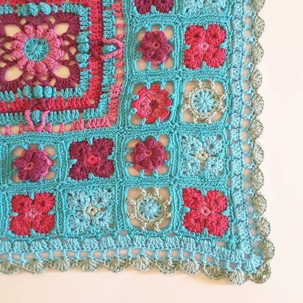 Tapete de crochê quadrado com flor azul e vermelha