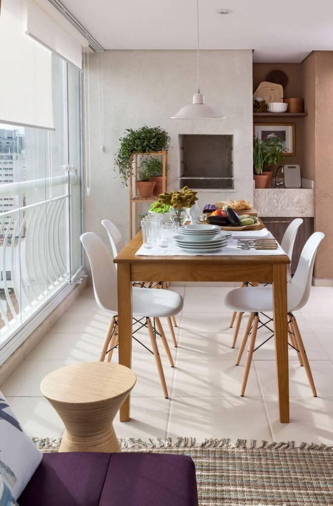 Varanda com churrasqueira e mesa de madeira