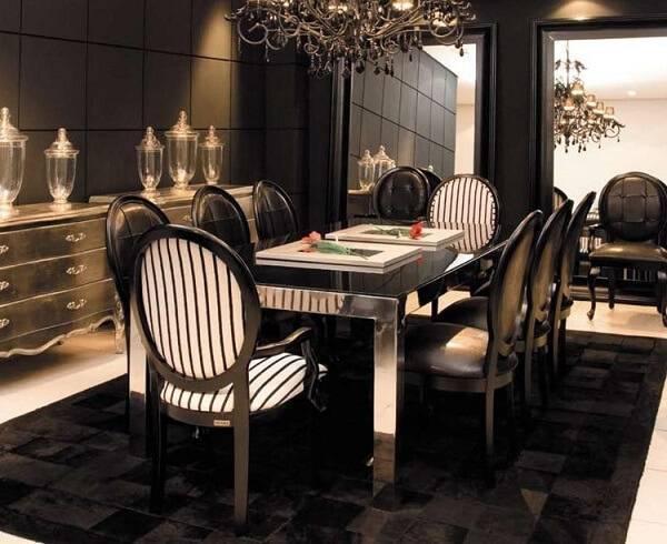 Sala de jantar sofisticada com lustre colonial e cadeira medalhão