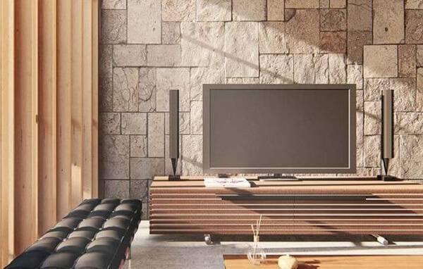 Sala de TV sofisticada com parede de pedra miracema