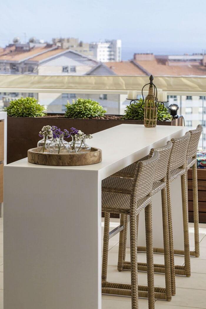As banquetas de fibra sintética e bancada branca são móveis para varanda perfeitos.