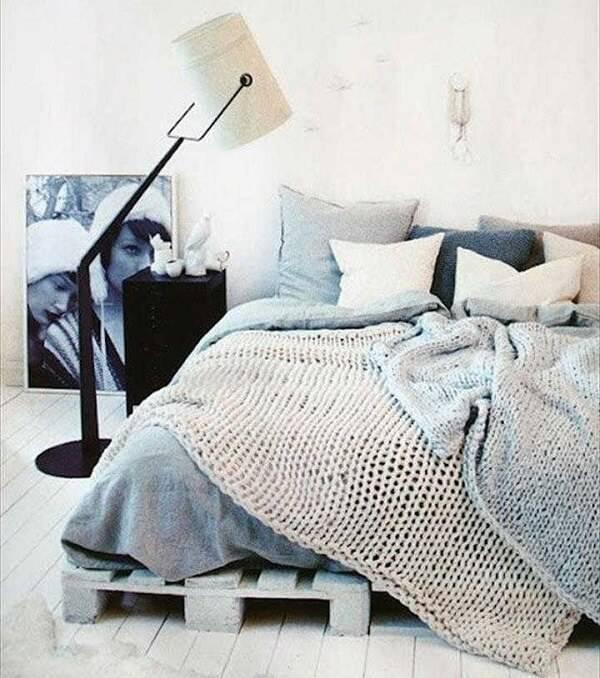 Quarto de casal com cama de pallet e luminária de piso