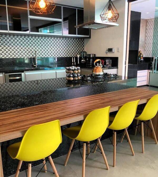Cozinha com bancada de granito verde Ubatuba e cadeiras Eiffel amarela