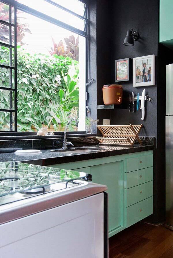 Cozinha com decoração descontraída e iluminada com janela grande e bancada de granito verde ubatuba