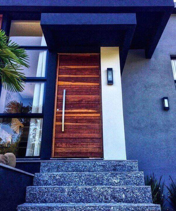 A pedra miracema cinza na escada traz neutralidade para a entrada da casa