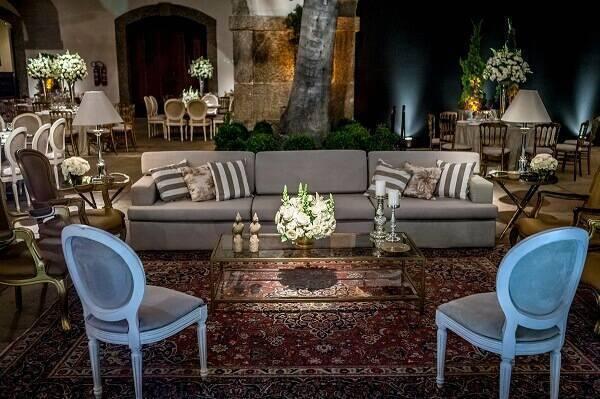 Sala de estar com sofá três lugares e cadeira do tipo medalhão azul