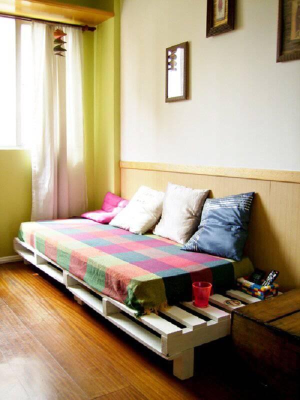 Sofá cama de pallet pintado de branco se harmoniza com a decoração do cômodo