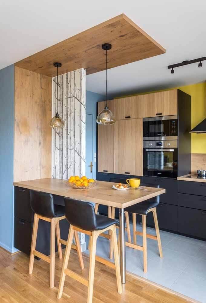 Balcão de cozinha de madeira com móveis pretos