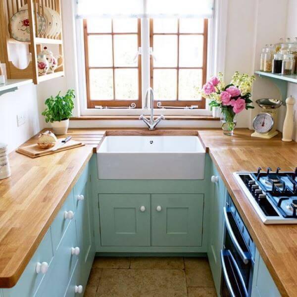 Cozinha de madeira com bancada e armários azuis