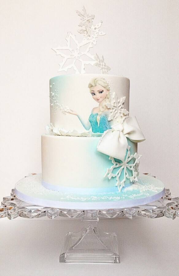 Frozen cake decoration with elsa design and snowflakes on top Photo My Party