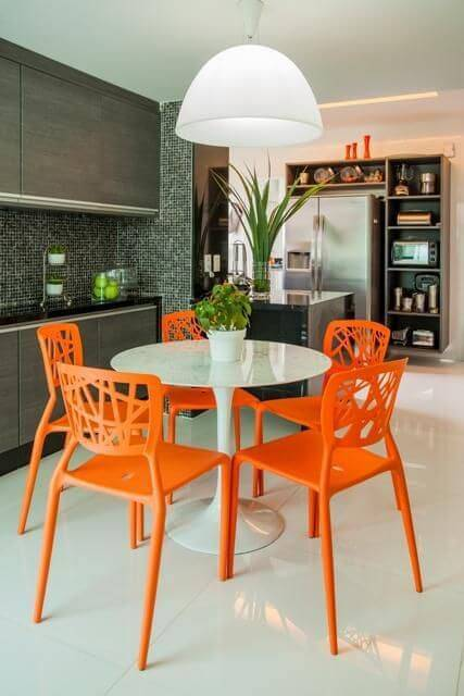 Cozinha alegre com cadeiras laranja e lustre para cozinha