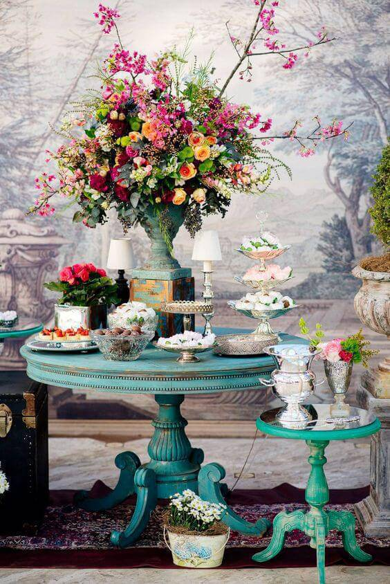 Decoração de festa em casa colorida com arranjos de flores e móveis antigos