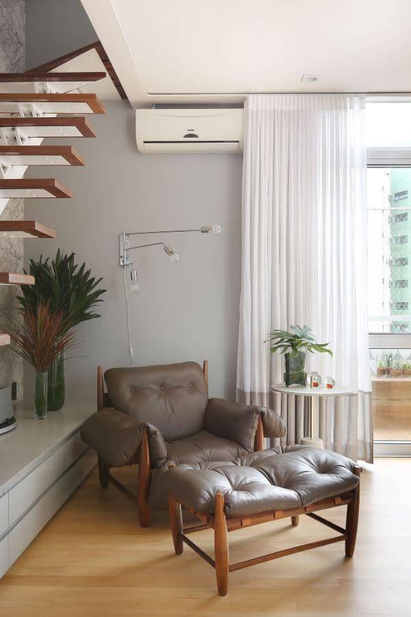 Sala de estar com poltrona mole no cantinho de leitura
