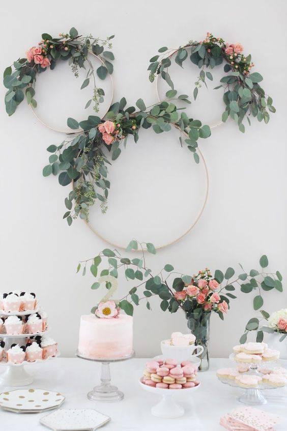 Festa em casa com arco de flores na mesa de doces