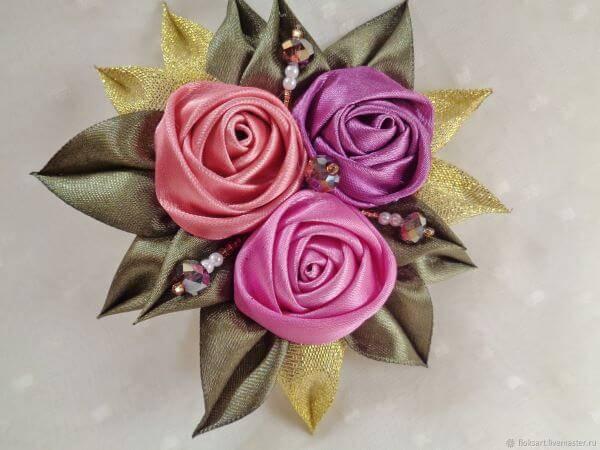 Flor de fita de cetim com pétalas e detalhes dourados