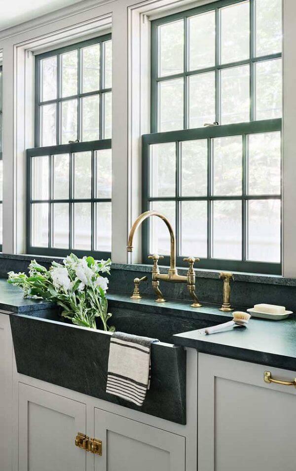 Cozinha iluminada com bancada extensa de granito verde ubatuba