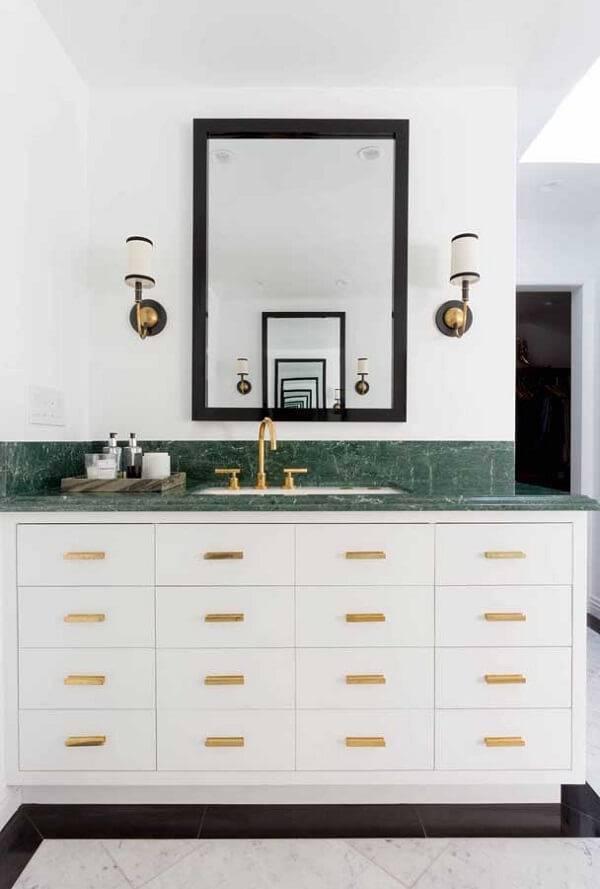Banheiro com decoração sofisticada em tons de branco, dourado e verde