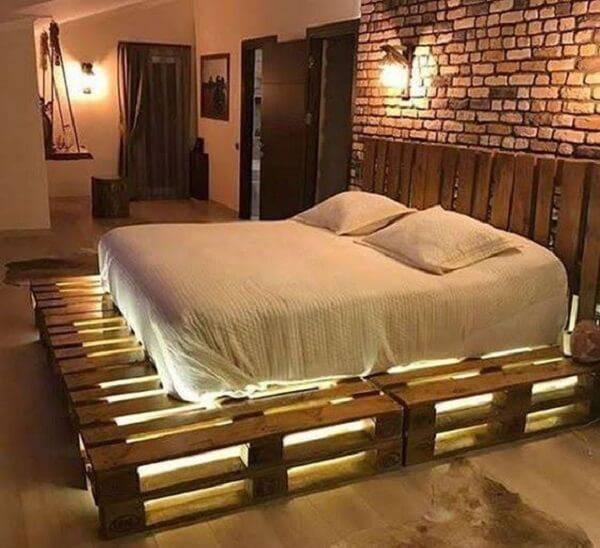 Quarto de casal com cama de pallet e iluminação especial