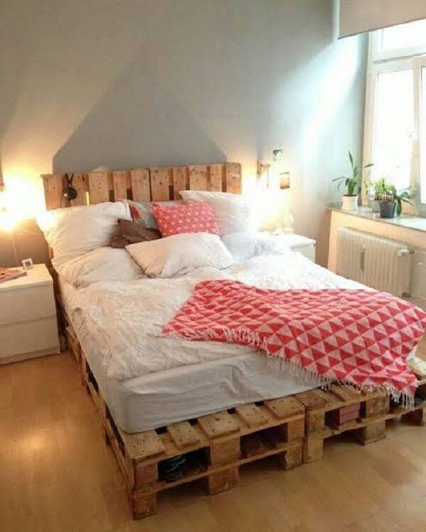 Quarto de casal iluminado com cama de pallet e luminárias
