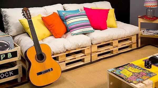 Sala de estar com sofá cama de pallet e almofadas coloridas