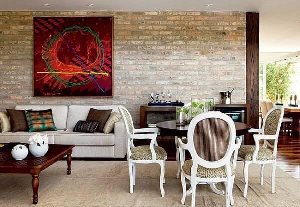 A parede de tijolinho aparente integra os ambientes da sala de jantar e sala de estar