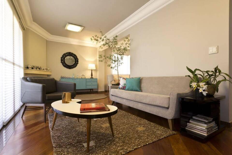 poltrona de madeira - mesa de centro de madeira e sofá de veludo cinza