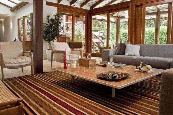 poltrona de madeira - mesa de centro de madeira e tapete listrado na sala