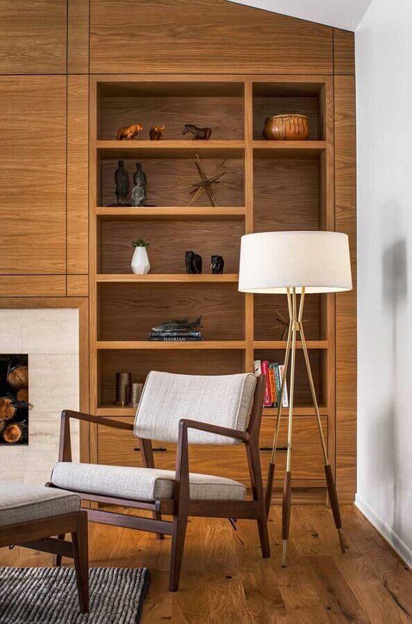 poltrona de madeira para sala decorada com estante de nichos e abajur de chão  Foto Richard Brown Architect