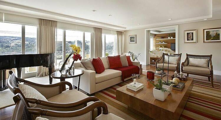 poltrona de madeira - tapete com listras em tons quentes e sofá branco