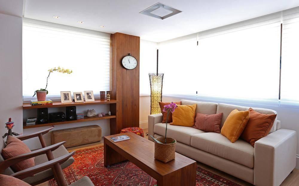 poltrona de madeira - tapete vermelho estampado e sofá estofado claro